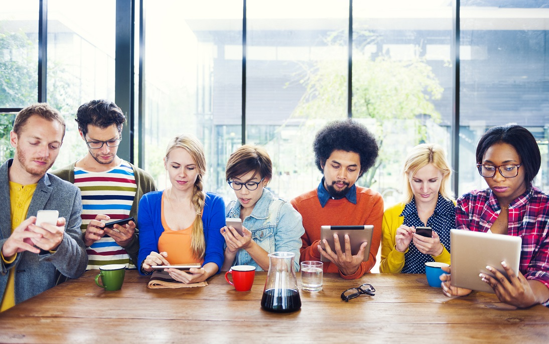 Group of millennials searching on mobile phones and tablets